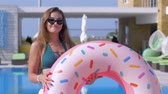uzun saçlı : beautiful glamorous girl into bathing suit and eyeglasses with inflatable rings flirts on camera near blue pool at expensive resort on summer vacation