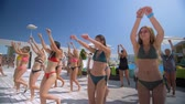 juvenil : LAZURNOE, UKRAINE- JULY 13, 2019: fun by the pool, young women relaxing in swimsuits at a luxury resort have fun repeating dances on morning exercises with animators