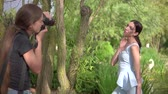 сессия : KHERSON, UKRAINE- JULY 04, 2019: professional woman photographer takes pictures of luxury fashion model in designer clothes photo shoot in a beautiful green park