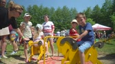 dinlenmek : KOZACHI LAGERYA, UKRAINE- JUNE 01, 2019: children entertainment, kids orphans have fun riding on swing in leisure park during childish holiday on family weekend, charity festival Stok Video