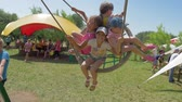 giostre : KOZACHI LAGERYA, UKRAINE- JUNE 01, 2019: children on swing, couple of joyful kids have fun laughing and amusement rides an park during holiday on summer vacation Filmati Stock