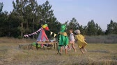 kinderen lopen : weekend games in forest, active kids running around in a clearing decorated with a wigwam catch each other in a dragon costume while relaxing on picnic Stockvideo
