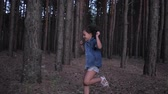 ragazza carina : childhood, merry little girl peeping out from behind a tree then runs between rows pines in forest during vacation at evening time
