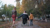 cadeira de rodas : family relationships, happy disabled person in wheelchair enjoys life together with a child and his wife raise their hands up while walking on beautiful autumn afternoon, rear view