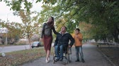 fauteuil roulant : family support, disabled husband in a wheelchair walks with his family on beautiful fall day through city streets