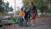 inválido : family walk, disabled father in a wheelchair carries his son on his knees walking in the autumn street with his smiling wife Vídeos