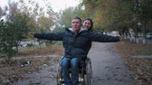 paralyzed : friendly support, happy disabled man have fun on a wheelchair ride a smiling female in autumn park