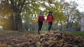 若々しい : friendships, two beautiful smiling girlfriends run holding hands and throw leaves in the autumn park in the fall season