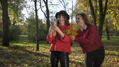 若々しい : fall season, funny seductive girls friends take pictures on phone against backdrop of autumn leaves in the park for a walk