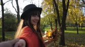 若々しい : follow me, young funny woman in hat runs cheerfully and holds the hand of friend during on a walk in fall season at autumn park