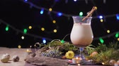 cravado : festive table, a beautiful glass with a traditional egg cocktail decorated with a christmas tree and lights, eggnog