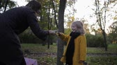 offspring : playing with a child, mom with a smiling girl have fun playing paper scissors in a stone for a walk in the autumn park Stock Footage