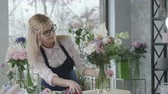 nemek : gender equality, young attractive blonde entrepreneur, owner of a successful small business, prepares modern fresh bouquets of flowers for sale and delivery in a flower shop, startup Stock mozgókép