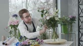 等しい : entrepreneur male florist loving job carefully selects flower composition for sale in modern flowering shop, success small business 動画素材