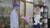 small business, a young attractive girl working in a flower shop gives a beautiful bouquet of flowers to a man from a delivery service, a concept of success