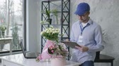 услуги : young man checks a list of orders from an online service for the delivery of fresh bouquets of flowers from a modern flower shop, concept of success