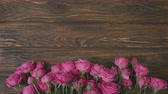 wooden background with pink flowers and copy space for text, florist lays bunch roses on a planks