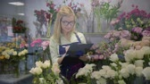 róża : portrait of a beautiful smiling girl professional florist owner of a small business working in a flower shop checks quality of flowers, a successful startup