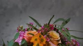 closeup of beautiful fresh flowers gathered in a creative modern bouquet by a young professional florist revolve a dark background for an inscription, floristry