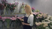 flower shop, portrait of young woman small business owner of floristic boutique checks flowers in a greenhouse smiling and looking at camera, florist