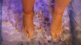 Young woman receiving massage with small fishes. Peeling with fish. Girl enjoying medicinal procedure. Foot massage with fish in aquarium closeup. Fish spa procedure Stok Video