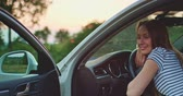 chegar : Traveler woman resting on a car wheel during a stop on road trip vacation travel. 4K DCi resolution. Young smiling woman relaxing in the car with sunlit backlit road in background. Slow motion.