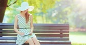 casual : Woman writing in a diary in the green park outdoors, Slow motion. Beautiful lady in a white hat making notes in her notebook, sitting on a bench, smiling and enjoying nature in a summer garden. 4K.