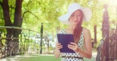 casual : Woman using digital tablet in the green park outdoors. Beautiful young lady, wearing a hat and a dress, using a modern tablet to search for information and communicate in summer. Slow motion. 4K, DCi.