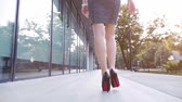 sensual : Sexy woman legs in black high heels shoes walking in the city urban street. Steadicam stabilized shot, Slow motion. Lens flare. Female legs in high-heeled shoes in the morning. Cinematic shot.