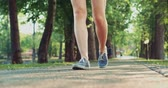 spring : Female feet in sneakers gumshoes walking and posing on a park road, close up. Womans feet in denim sports shoes passing by the camera. Slow motion, 120fps. 4K, DCi. Stock Footage