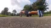 male in sportswear doing push ups. Outdoors workout . back view Wideo