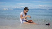 estrellitas : Girl sitting in the tropical sea, the waves rolled on her feet, she holds a starfish.
