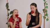 lolipop : Young girls sitting on the swing and enjoy candy.Young girls sit on a swing and eat lollipop. Stok Video