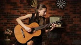 rock'çı : Young girl in black dress playing guitar in the dark romantic room.Young girl playing music on acoustic guitar.
