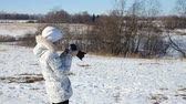 momentka : Girl with the camera photographs the landscape in winter day.young girls photographing outdoors. Dostupné videozáznamy