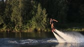 pairar : Man on the flying board on the river, water jet spray.Man on the flying board flies over the lake water.Fly board rider.