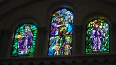 intramuros : Multicolored stained glass church window illustrated Bible stories. stained glass windows with religious motifs. Manila Cathedral interior, Intramuros. 4K video, Philippines