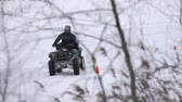 bike ride : ATV race on the snow. Rider driving in the quadbike race. Man riding ATV in sand in protective clothing and a helmet. Racer rides a quad motorbike in the cross racing. Quadrocycle on the snow cover. Slow motion.