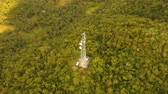 передатчик : Communication tower, cellphone tower in the jungle in the mountains. Aerial view: satellite, cellphone tower, on a mountain. View of a tropical island with palm trees and other vegetation, a mountain and white telecom radio tower. 4K video. Aerial footage Стоковые видеозаписи