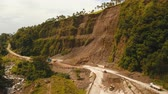 landslide : Landslides and rockfalls on the road in the mountains.Aerial view: mud and rocks blocking the road.Destroyed rural road landslide damaged in powerful flood. Collapsed on the mountain. Philippines, Camiguin. 4K video. Aerial footage.