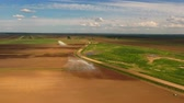 разбрызгиватель : Irrigation equipment watering freshly seeded field.Rainbow by irrigation.Irrigation of farmland to ensure the quality of the crop.Aerial view:irrigation system watering a farm field.
