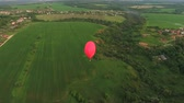 дирижабль : Red balloon in the shape of a heart.Aerial view:Hot air balloon in the sky over a field in the countryside, beautiful sky and sunset. Aerostat fly in the countryside. 4K video,ultra HD.