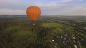 дирижабль : Aerial view:Hot air balloon in the sky over a field in the countryside in the beautiful sky and sunset.Aerostat fly on the countryside. 4K video,ultra HD.