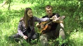 kytarista : girl loves her father to play an acoustic guitar garden. Father and his young daughter are playing a guitar in a green park. 4K video