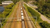 wagons : Freight train with cisterns and containers on the railway. Aerial view Container Freight Train, Locomotive to the railway station. 4K, flying video, aerial footage.