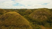 geológico : Amazingly shaped Chocolate hills on sunny day on Bohol island, Philippines. Aerial view Chocolate Hills in Bohol, Philippines are earth mounds scattered all over the town of Carmen. 4K video. Travel concept. Aerial footage. Stock Footage
