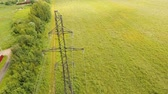 tensão : Power pylons and high voltage lines in an agricultural landscape. Aerial view row of high-voltage masts in the field. Electricity transmission power lines. Aerial footage.