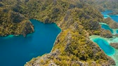 busuanga : Aerial view: Mountain Barracuda lake, on tropical island, Lagoon with blue, azure water. Lake in the mountains covered with tropical forest on the island Coron, Palawan, Philippines. 4K video, Travel concept, Aerial footage.