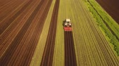 plowed field : Aerial view Farmer in tractor preparing land with seedbed cultivator in farmlands. Tractor plows a field. Agricultural work in processing, cultivation of land. Farmers preparing land and fertilizing. Agricultural workers with tractors. 4K, flying video, a