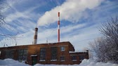 high power : Boiler room in the winter season, from the chimneys rise up clouds of steam. Pipes of a thermal power plant. Boiler house, pipe plant, boiler plant. 4K video. Stock Footage